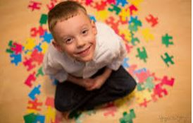 image of a boy sitting and looking up, smiling around puzzle pieces